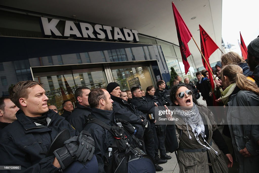 Anti-capitalism protesters demonstrate outside a Karstadt department store as riot police look on during Blockupy protests in the Zeil pedestrian shopping street on May 31, 2013 in Frankfurt am Main, Germany. Several thousand protesters are taking part in Blockupy protests today and tomorrow in Frankfurt in order to demonstrate aginst ECB debt policy, food prices speculation by Deutsche Bank and the labor practices inherent in the discount clothing industry.