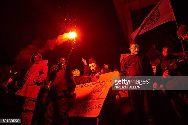 Anticapitalist activists wearing masks hold a lit flare as they gather ahead of the 'Million Masks March' organised by the group Anonymous at...