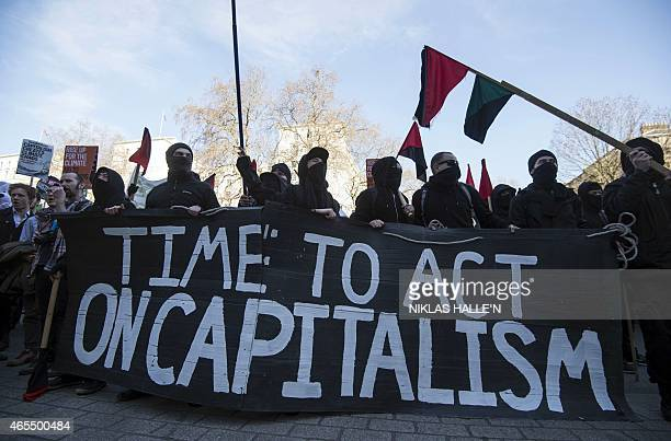 Anticapitalist demonstrators display a banner reading 'Time to act on Capitalism' outside Downing Street during The People's Climate march in central...