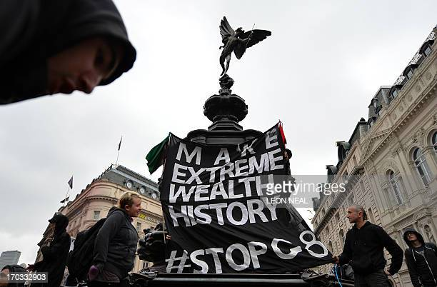 Anticapitalist protesters hang a banner underneath the statue of Eros in Piccadilly Circus in central London on June 11 during protests ahead of the...