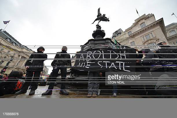 Anticapitalist protesters hold a banner underneath the statue of Eros in Piccadilly Circus in central London on June 11 during protests ahead of the...