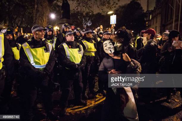 Anticapitalist protesters wearing Guy Fawkes masks embrace in front of a line of British police officers during the 'Million Masks March' organised...