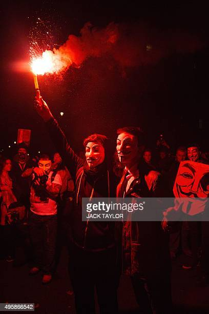 Anticapitalist protesters wearing Guy Fawkes masks hold a flare during the 'Million Masks March' organised by the group Anonymous in London on...