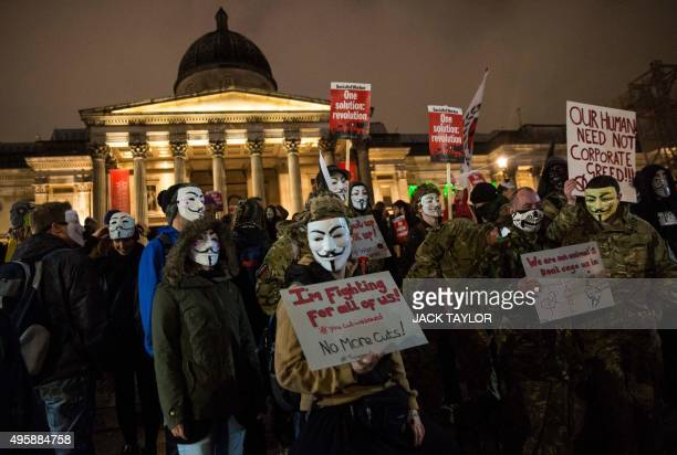 Anticapitalist protesters wearing Guy Fawkes masks hold placards at the start of the 'Million Masks March' organised by the group Anonymous at...