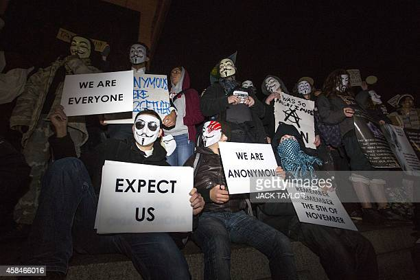 Anticapitalist protesters wearing Guy Fawkes masks hold placards during the 'Million Masks March' organised by group Anonymous at Trafalgar Square in...