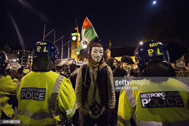 Anticapitalist protesters wearing Guy Fawkes masks take part in the 'Million Masks March' in Parliament Square in London on November 5 2014 The...