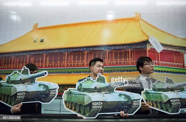 AntiChina activists hold tank placards representing the 1989 Tiananmen Square crackdown while protesting in front of an advertisment of The Hong Kong...