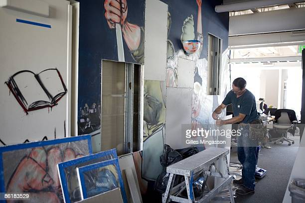 Anticipating a move to larger offices in the future as the company grows a worker carefullly removes original graffiti from the Facebook headquarters...