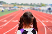 """""""A picture of a youth girl at the starting line, about to compete in a track & field event."""""""
