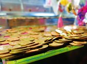 Copper coins teeter on the brink inside a fairground coin pusher machine