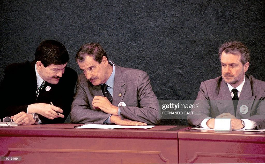 Anticorruption czar Francisco Barrio talks with Mexican President Vicente Fox watched by Interior Secretary Santiago Creel during the signature of...