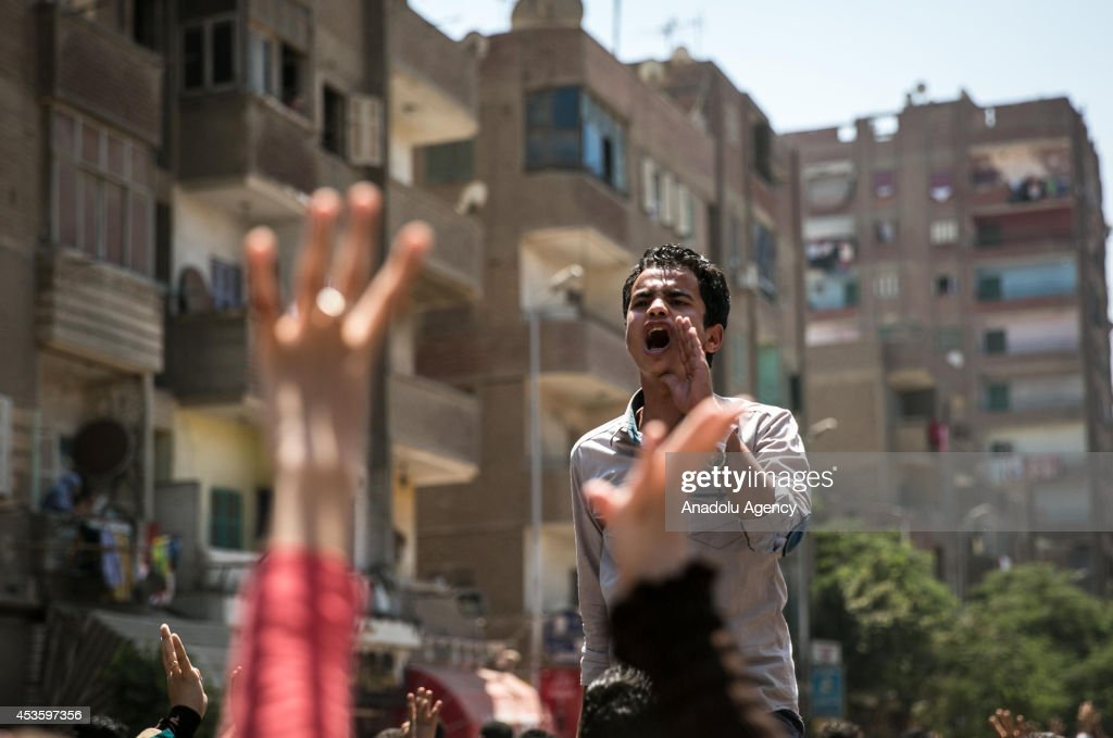 Anticoup demonstrators shout slogans as they march at Al Haram Street during a demonstration on World Rabaa Day marking the 1st anniversary of the...