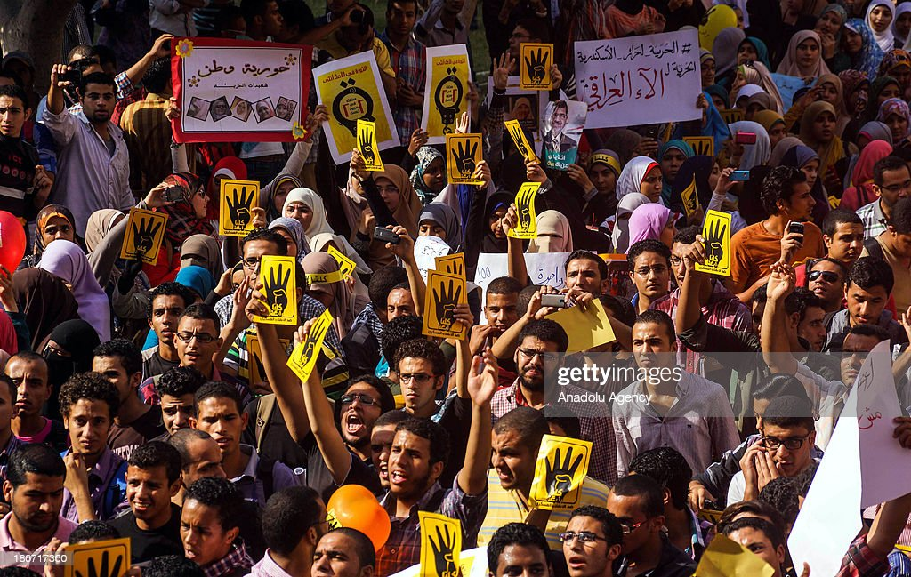 Anti-coup students of Alexandria University shout slogans and hold up signs during a demonstration on November 3, 2013 in Alexandria, Egypt to call for the release of the student being detained while protesting against military coup.