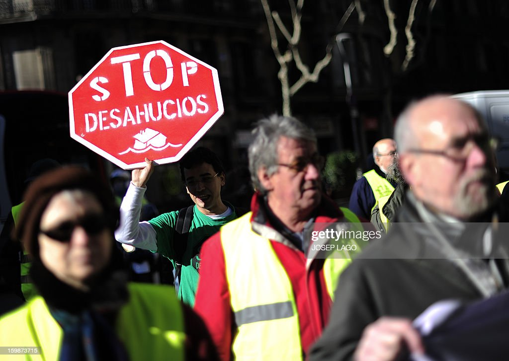 Anti-eviction activists and members of the 'iaioflautas' organization gather outside the Spanish Government Delegation headquarters to protest against evictions in Barcelona on January 22, 2013. The placard reads: 'Stop evictions'