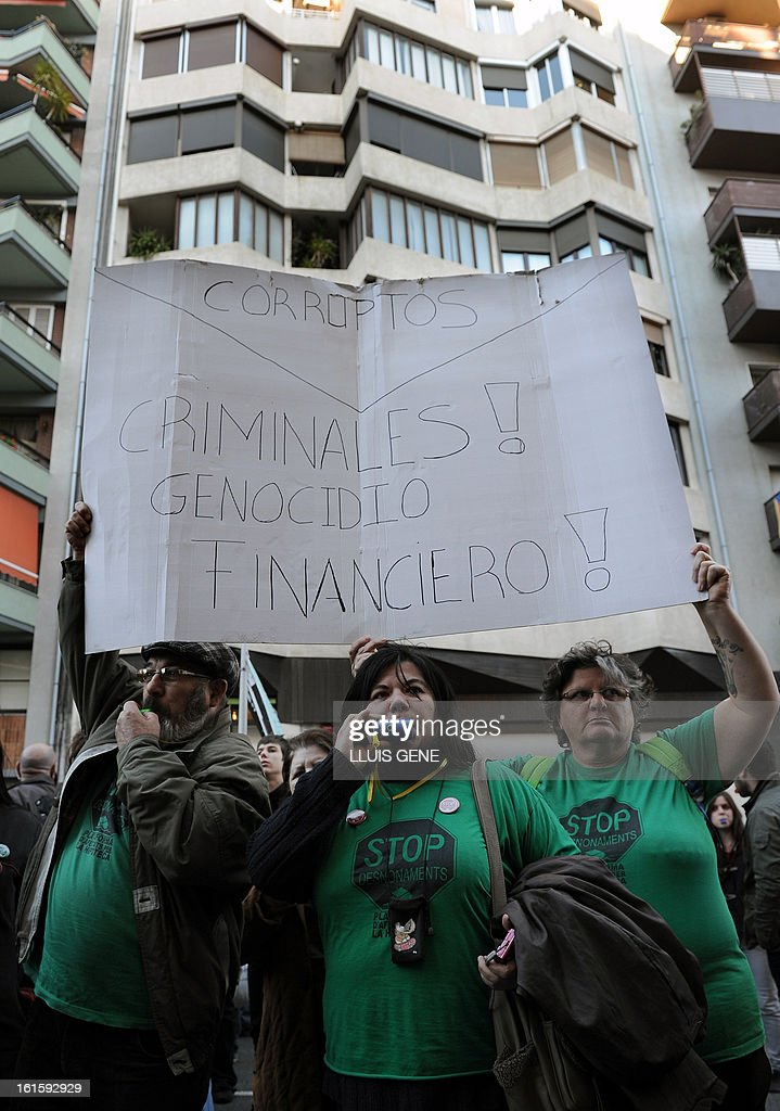 Anti-eviction activists hold a placard reading 'Corrupted! Criminals! Finance genocide!' as they take part in a protest in front of the Popular Party's (PP) headquarters in Barcelona on February 12, 2013.