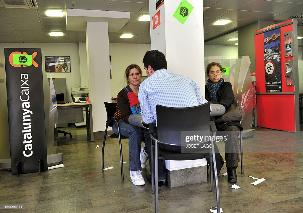 Anti-eviction activists of the PAH (Platform of People Affected by Mortgage) Jose Manuel, Miriam and Carmeli chain themselves in a Catalunya Caixa Bank office during a protest against mortgage debt on January 24, 2013 in Barcelona. Protests are growing in Spain as people decry an economic slump, unemployment and a series of austerity measures adopted by Prime Minister Mariano Rajoy's right-leaning government.