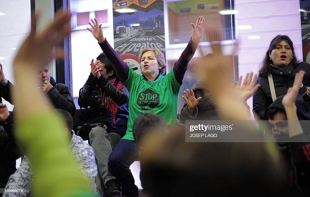 Anti-eviction activists of the PAH (Platform of People Affected by Mortgage) protest in a Catalunya Caixa Bank office against mortgage debt on January 24, 2013 in Barcelona. Protests are growing in Spain as people decry an economic slump, unemployment and a series of austerity measures adopted by Prime Minister Mariano Rajoy's right-leaning government.