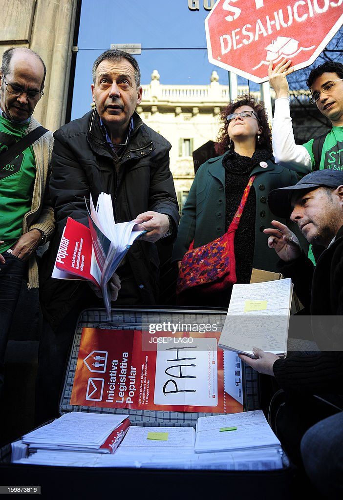 Anti-eviction activists of the PAH (the Platform of People Affected by Mortgage) show signatures they gathered for a Popular Legislative Initiative (ILP) to stop evictions, regulate dation-in-payment and establish social rents, during a demonstration organized by anti-eviction activists and members of the 'iaioflautas' organization at the Spanish Government Delegation headquarters in Barcelona on January 22, 2013.