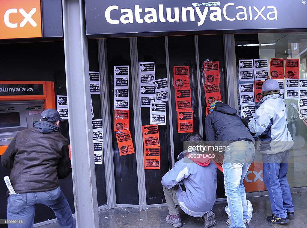 Anti-eviction activists of the PAH (Platform of People Affected by Mortgage) stick placards reading 'This bank steals' in the window of a Catalunya Caixa Bank office during a protest against mortgage debt on January 24, 2013 in Barcelona. Protests are growing in Spain as people decry an economic slump, unemployment and a series of austerity measures adopted by Prime Minister Mariano Rajoy's right-leaning government. AFP PHOTO / JOSEP LAGO