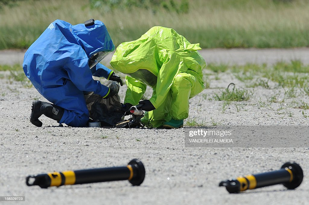 Anti-explosives experts from a police commandos from an anti-kidnapping unit, deactivate a bomb during a drill at the Tom Jobim International Airport in Rio de Janeiro, Brazil, on January 13, 2012, ahead of the FIFA World Cup Brazil 2014 and the 2016 Olympic Games.
