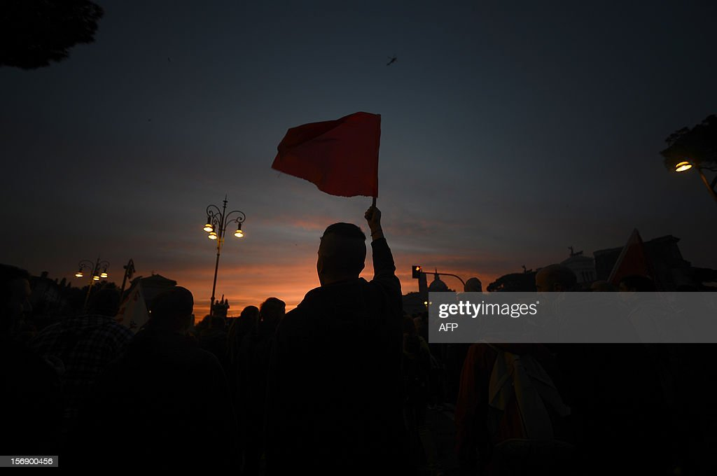 Anti-fascist demonstrators wave a flag as they march near the Colosseo prior a demonstration of far-right suporters on November 24, 2012 in Rome. AFP PHOTO / FILIPPO MONTEFORTE