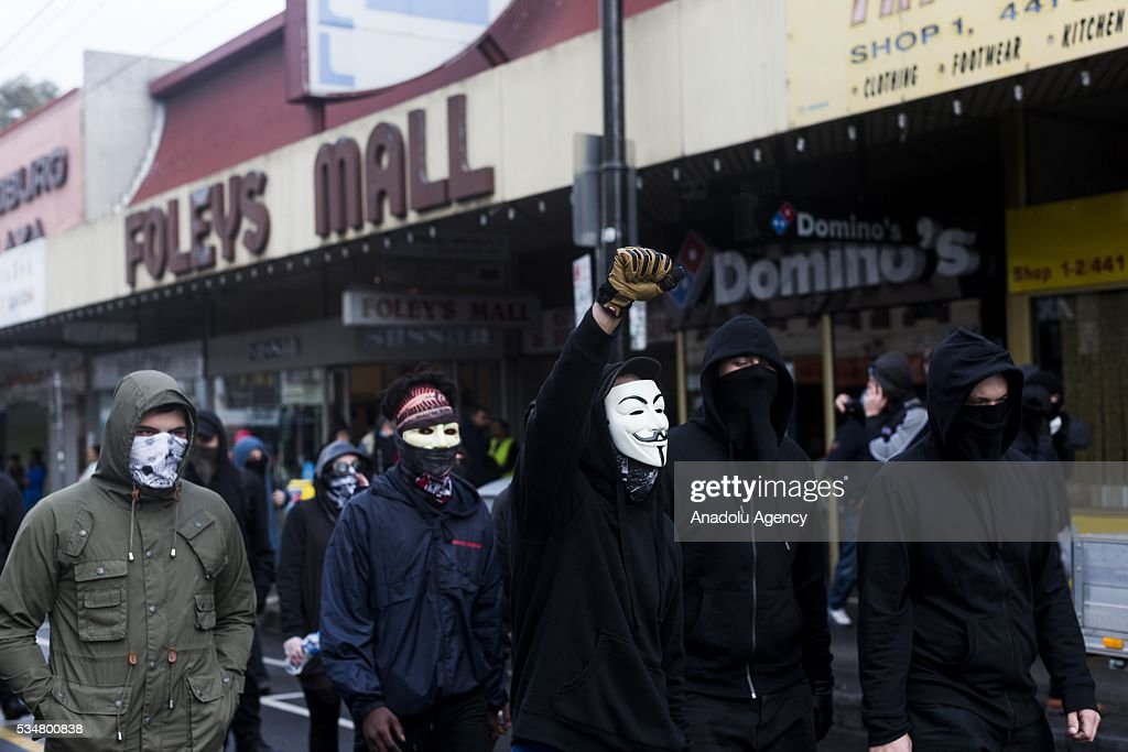 Antifascist protestors wearing masks and hooded tops march down the main street in coburg as a man in a guy fawkes mask clenches his fist in the air during a 'Say No To Racism' protest and a counter 'Stop the Far Left' rally in Coburg Melbourne, Australia on May 28, 2016. Seven men were arrested after a violent brawl erupted between rival protesters at an anti-racism rally in Melbourne's inner-north. Anti-Facists clashed with Anti-Islam nationalists who go by the name 'True Blue Crew'.