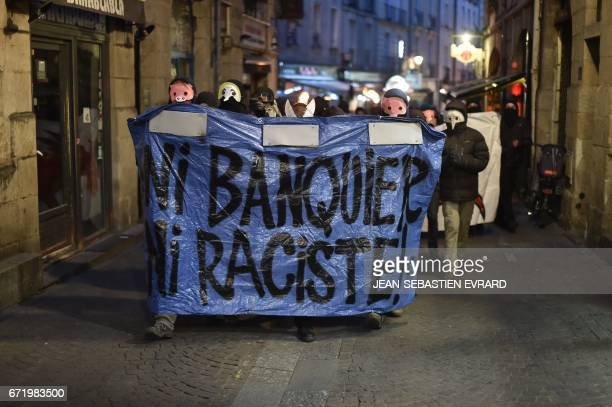 TOPSHOT Antifascists march with a banner which translates as 'Not Banker nor Racist' during a demonstration in Nantes western France on April 23 2017...