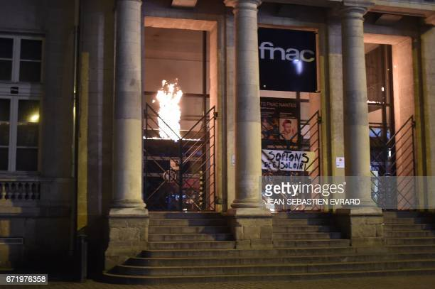 Antifascists set a store on fire during clashes with antiriot police forces as they demonstrate in Nantes western France on April 23 2017 following...