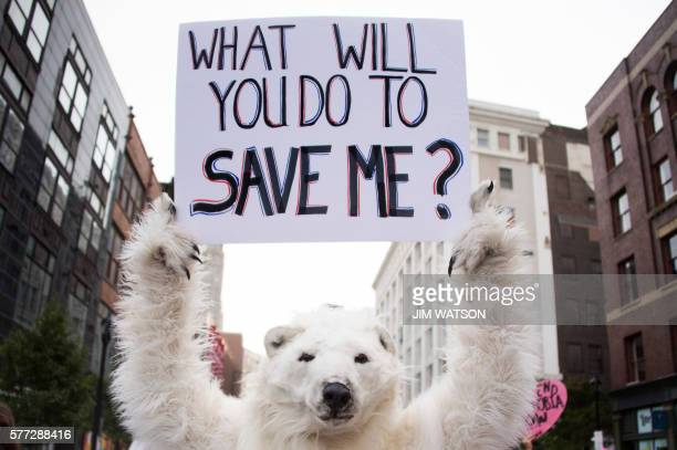 TOPSHOT A antiglobal warming protester holds up a placard in Cleveland Ohio near the Republican National Convention site July 18 2016 The Republican...