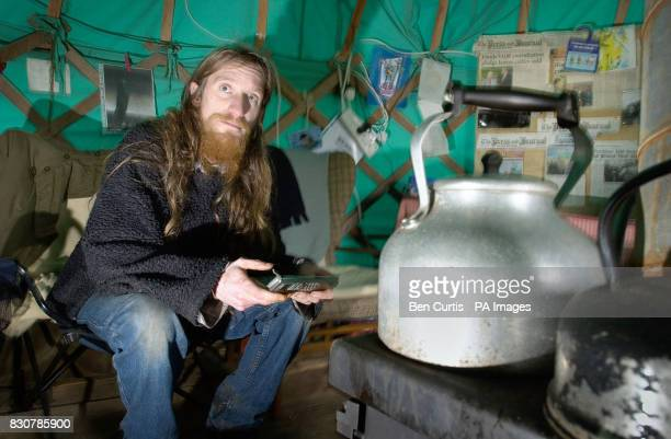 AntiGM crop protester Anthony Jackson writes emails from his mobile phone inside the 'yurt' tent at a site near Munlochy on the Black Isle in...