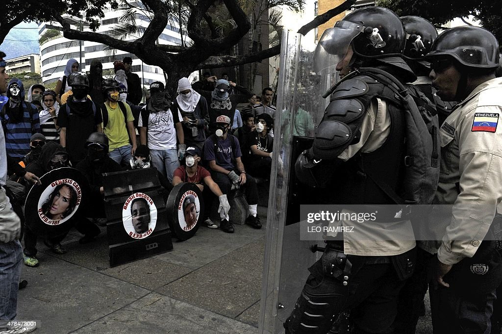 Antigovernment activists face riot squad officers while holding shields portraying pictures of people killed during recent protests in Caracas on March 13, 2014. Three more people were killed recently, raising the death toll from weeks of anti-government demos to 24.
