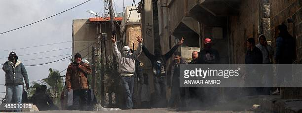 Antigovernment activists gestures as they gather on the streets of Daraa 100kms south of the capital Damascus on March 23 2011 Syrian security forces...