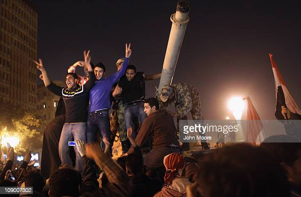 Antigovernment demonstrators celebrate on top of an army tank upon hearing the news of the resignation of Egyptian President Hosni Mubarak on...