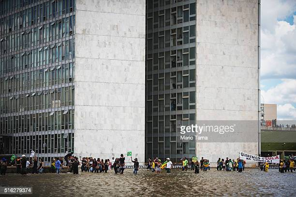 Antigovernment demonstrators march through the water in front of the National Congress building during demonstrations on March 17 2016 in Brasilia...