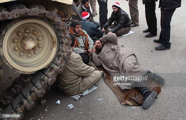 Antigovernment demonstrators rest while blocking an Egyptian army tank in Tahrir Square on February 5 2011 in Cairo Egypt Demonstrators who remained...