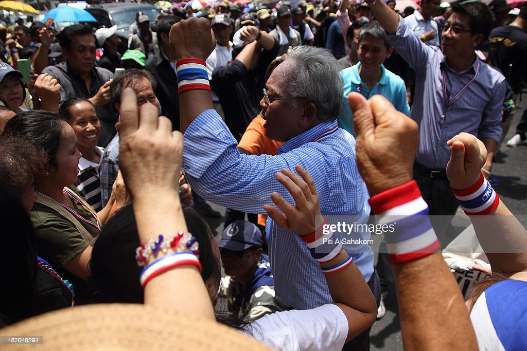 Anti-government leader Suthep Thaugsuban cheers with his supporters during a march on a street in Bangkok. Anti-government protests resumed with a rally in central Bangkok, where protesters vowed to bring down the government of caretaker Prime Minister Yingluck Shinawatra. The Election Commission has called a meeting of all political parties to discuss the timetable for the country's next polls, after the results of the 02 February 2014 general elections were annulled.