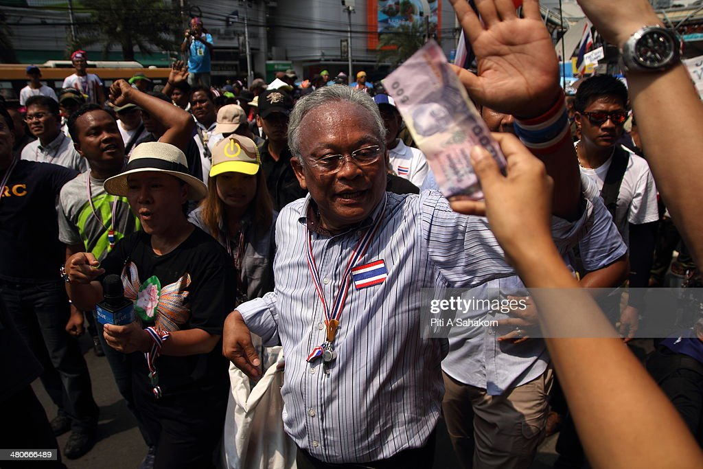 Anti-government leader <a gi-track='captionPersonalityLinkClicked' href=/galleries/search?phrase=Suthep+Thaugsuban&family=editorial&specificpeople=5734971 ng-click='$event.stopPropagation()'>Suthep Thaugsuban</a> receives money donated by supporters during a march on a main street in Bangkok. Anti-government protesters returned to the streets of Bangkok, warming-up for a big rally planned for the 29th March 2014. Anti-government leader <a gi-track='captionPersonalityLinkClicked' href=/galleries/search?phrase=Suthep+Thaugsuban&family=editorial&specificpeople=5734971 ng-click='$event.stopPropagation()'>Suthep Thaugsuban</a> vowed to oppose any election until political reforms are instituted to end what he sees as the corrupt influence of caretaker Thai premier Yingluck Shinawatra. Thailand's Constitutional Court annulled the 02 February 2014 general election which was boycotted by the opposition Democrat Party and voting booths were blocked by anti-government protesters.