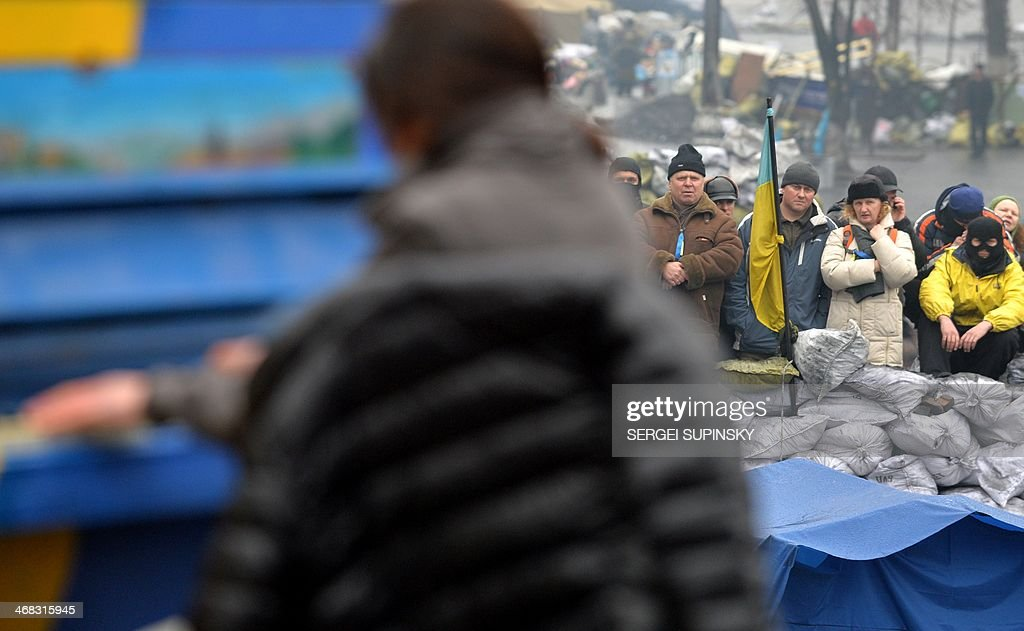 Anti-government opposition activists listen to Ukrainian musician Ruslana Lyzhychko known as Ruslana, a World Music Award winner, MTV Europe Music Award nominated artist and the winner of the 2004 Eurovision Song Contest, as she performs on an anti-government barricade in central Kiev during a concert organized for the activists and the policemen on February 10, 2014. Russia will release the next instalment of its $15-billion loan to Ukraine at the end of the month, a newspaper close to President Viktor Yanukovych said on February 10, following talks between Ukraine's leader and his Russian counterpart.