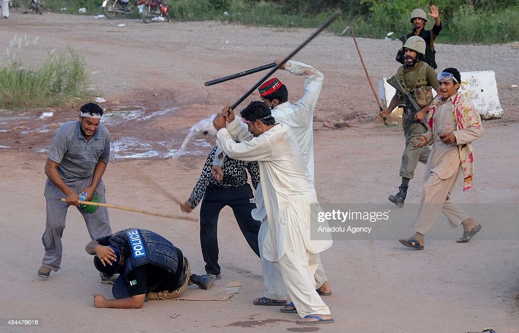 Anti-government protesters armed with batons, beat a policeman during clashes in Islamabad, Pakistan on September 1, 2014. Clashes erupted between the Pakistani riot police and anti-government protesters of Imran Khan, leader of Pakistan Tehreek-e-Insaaf (PTI), and Tahir-ul-Qadri, leader of Pakistan Awami Tehreek (PAT), during the ongoing anti-government protests in Islamabad.