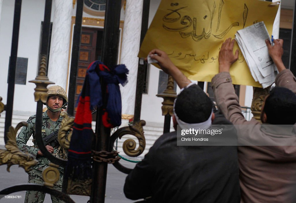 Anti-government protesters attach a sign to the gate of the Egyptian Parliament building as an Egyptian Army soldier guards inside on February 9, 2011 in Cairo, Egypt. Thousands of Egyptians protested outside of the parliament building in downtown Cairo to demand the assembly's immediate dissolution following waves of anti-government protests in the nearby Tahrir Square.