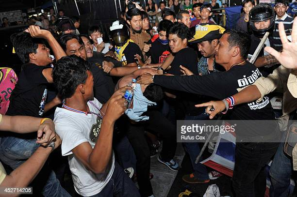 Antigovernment protesters attack a suspected Red Shirt supporter near Rajamala Stadium on November 30 2013 in Bangkok Thailand Supporters from either...