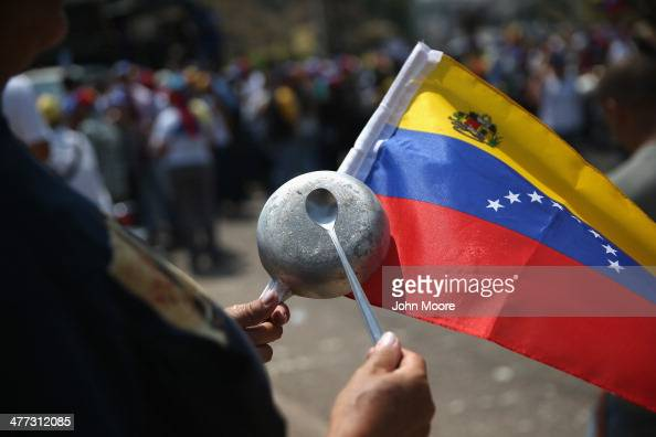 Antigovernment protesters bang pots and pans while marching on March 8 2014 in San Cristobal the capital of Tachira state Venezuela Shortage of such...
