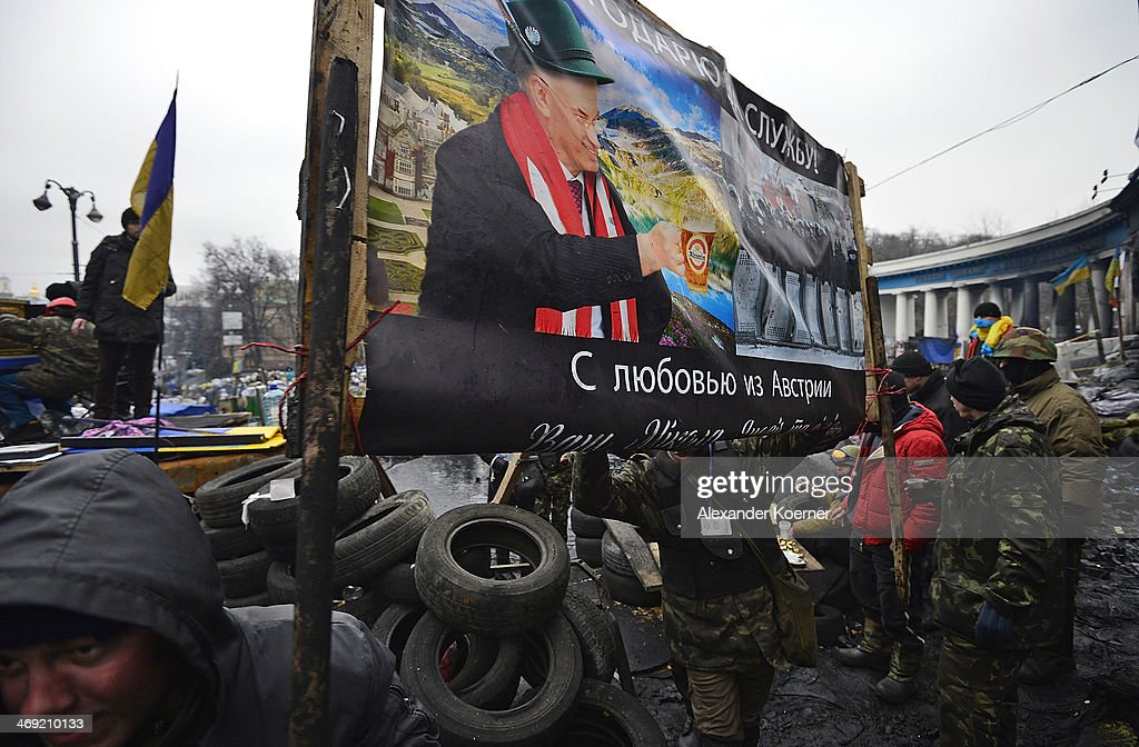 Anti-government protesters carry a billboard inside a barricade on Grushevskogo Street on February 13, 2014 in Kiev, Ukraine. Opposition party leader of UDAR Vitali Klitschko called out a national strike for today across the Ukraine.