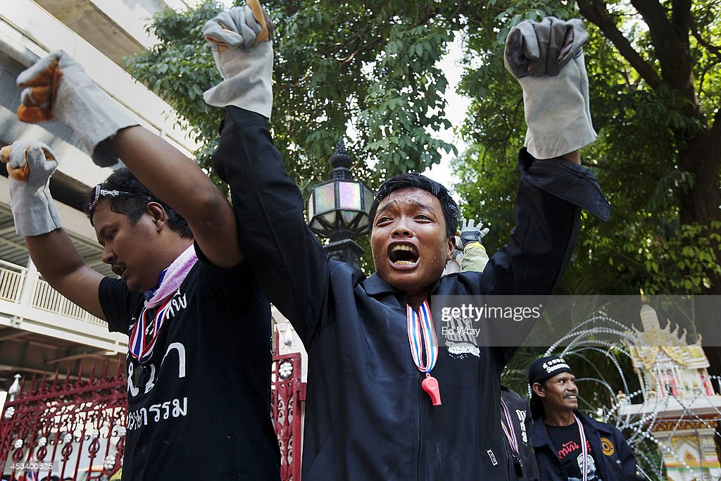Anti-government protesters cheer after breaking through a barricade at the central police headquarters during a demonstration on December 4, 2013 in Bangkok, Thailand. The protesters continued their demonstration, though in keeping with the relative calm after several days of violent clashes with police, there was no violence.