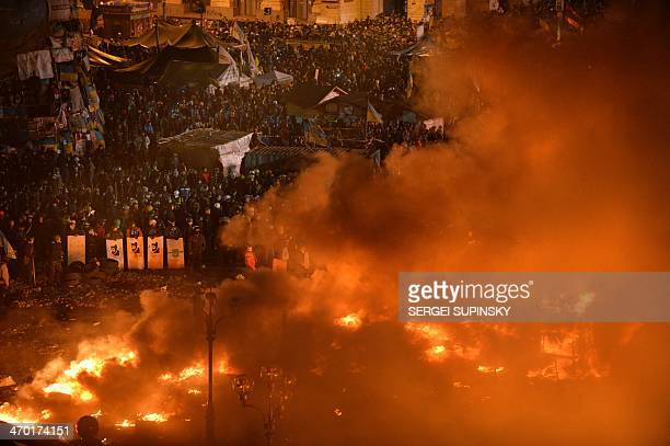 Antigovernment protesters clash with the police during their storming of Independence Square in Kiev on February 18 2014 Flames engulfed the main...