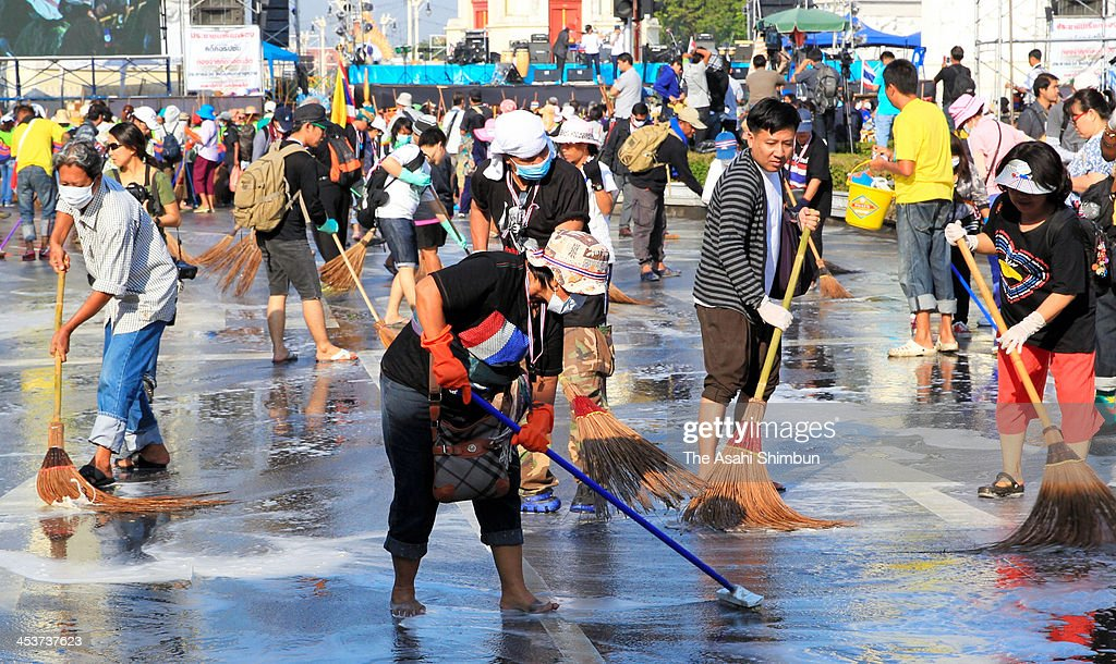 Anti-government protesters clean up the street around the Democracy Monument ahead of the birthday of Thai King Bhumibol Adulydej, on December 4, 2013 in Bongkok, Thailand. Tension between anti-government protesters and police have largely calmed after days of violent clashes in advance of the Thai King's birthday.