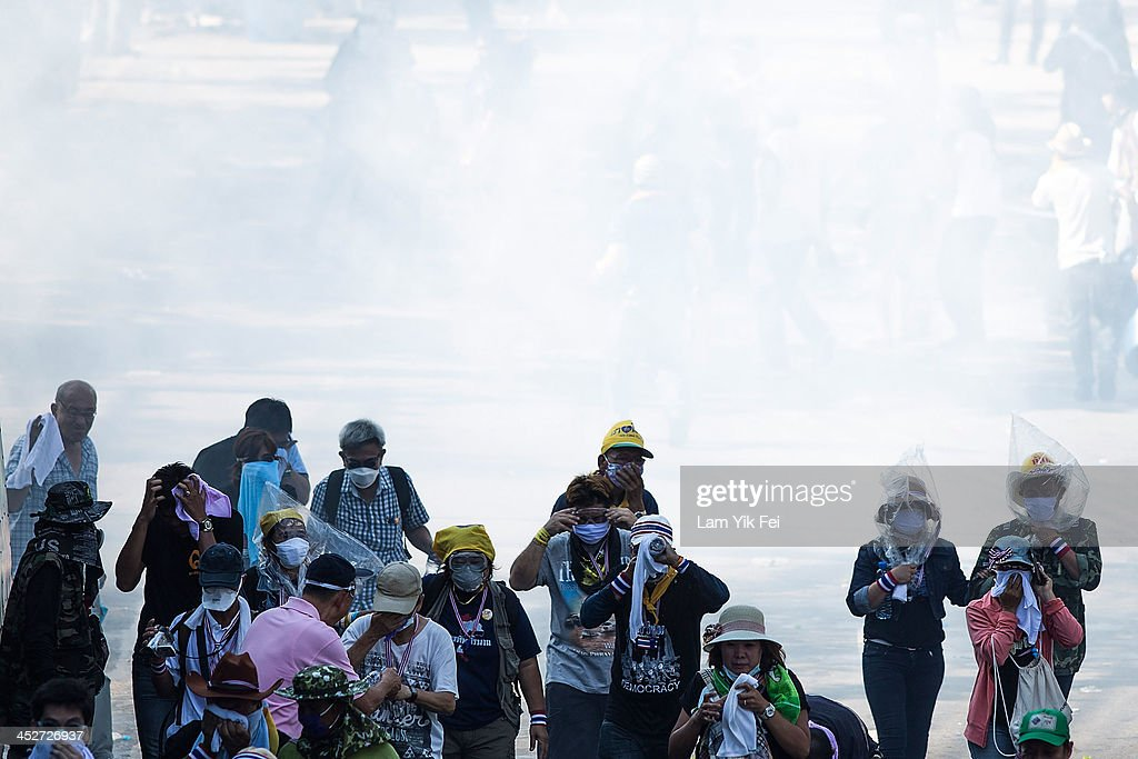 Anti-government protesters escape after riot police fire tear gas on December 1, 2013 in Bangkok, Thailand. Anti-government protesters in Bangkok say they plan to occupy the government house and the zoo, demonstrators calling on the government to step down have marched on ministries and government bodies in an attempt to shut them down.