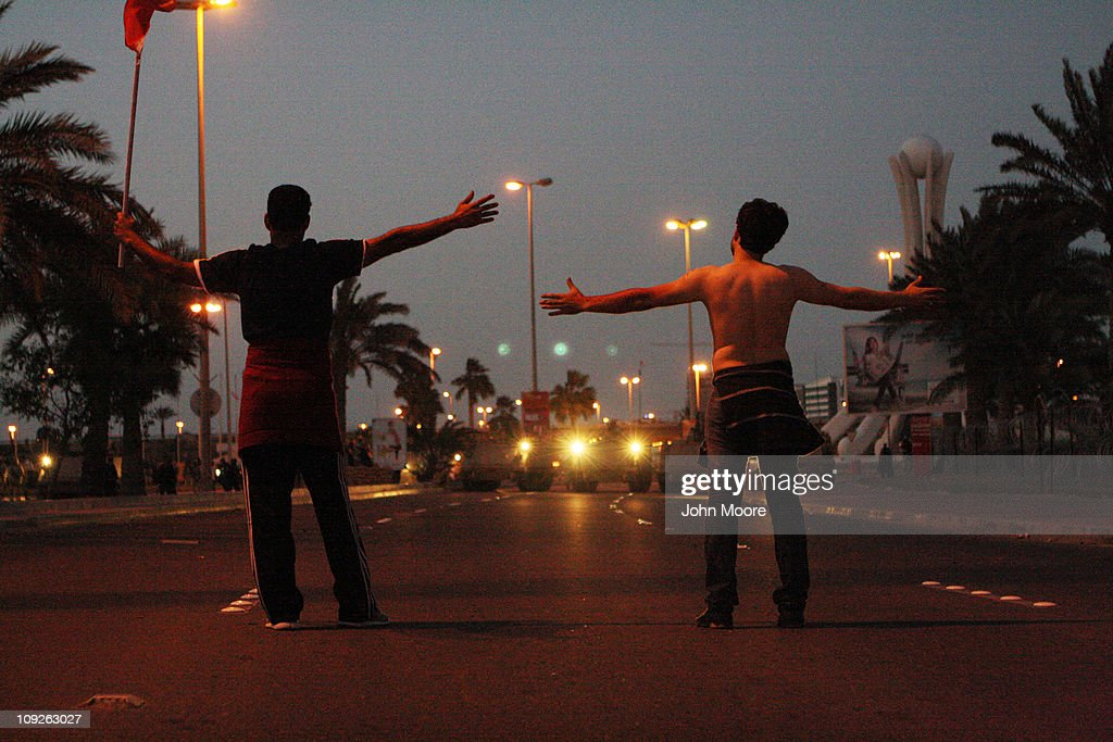 Anti-government protesters face off against the Bahraini army near the Pearl roundabout at dusk on February 18, 2011 in Manama, Bahrain. Protesters said that the army fired on them with live rounds, followed by teargas which drove the demonstrators back. There are unconfirmed reports that there are four dead in the clashes.