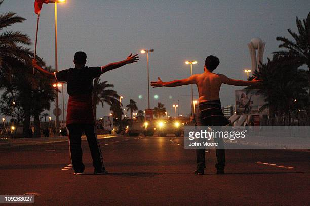 Antigovernment protesters face off against the Bahraini army near the Pearl roundabout at dusk on February 18 2011 in Manama Bahrain Protesters said...
