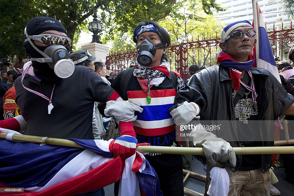 Anti-government protesters hold back the crowd while others try to break through a barricade at the central police headquarters during a demonstration on December 4, 2013 in Bangkok, Thailand. The protesters continued their demonstration, though in keeping with the relative calm after several days of violent clashes with police, there was no violence.